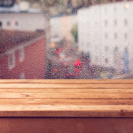 Empty wooden deck table over window with rain drops Stock Photo