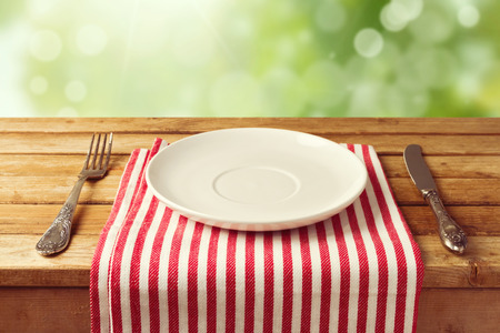 Empty plate with knife and fork on tablecloth over garden bokeh background