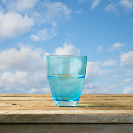 Glass of water on wooden table over blue sky