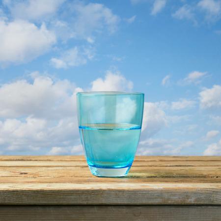 Glas water op houten tafel over blauwe hemel Stockfoto