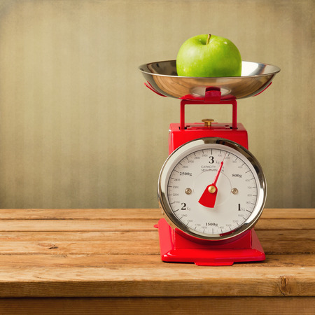 kitchen scale: Apple on vintage scale on wooden table Stock Photo