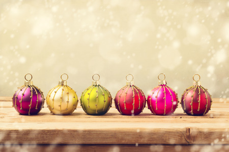 background cover: Christmas baubles on wooden table over golden bokeh background Stock Photo