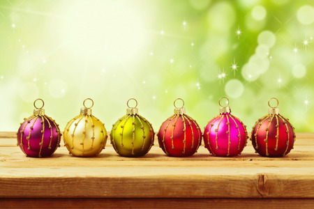 Christmas decoration balls on wooden table over green bokeh background photo