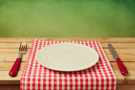 empty table: Empty plate with knife and fork on checked tablecloth over green background