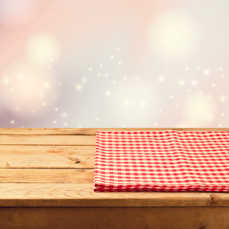 tablecloth: Christmas festive bokeh background with empty wooden table and red checked tablecloth