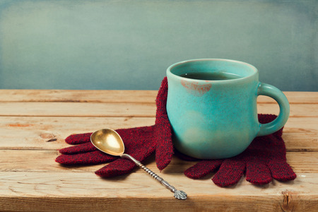 tea table: Cup of tea with lipstick stain and wool gloves on wooden table