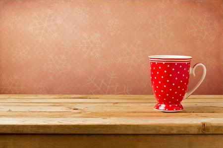 lunares rojos: Red lunares taza en la mesa de madera sobre fondo de pantalla con los copos de nieve
