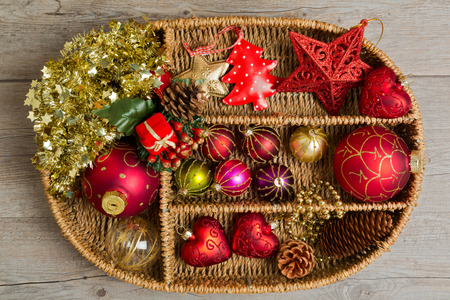 Christmas decorations in wicker box over wooden background photo