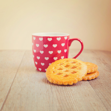 tea filter: Cup of tea and cookies with retro filter Stock Photo