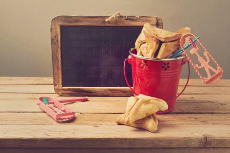 hamantaschen: Hamantaschen cookies in bucket with grogger and chalkboard