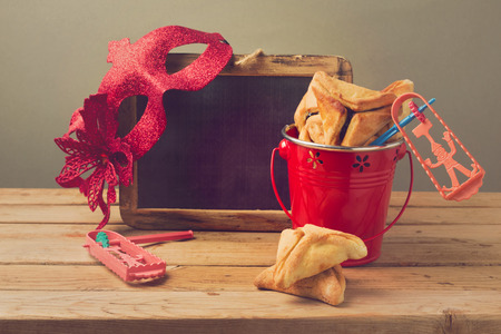 hamantaschen: Hamantaschen cookies in bucket with grogge, chalkboard and carnival mask