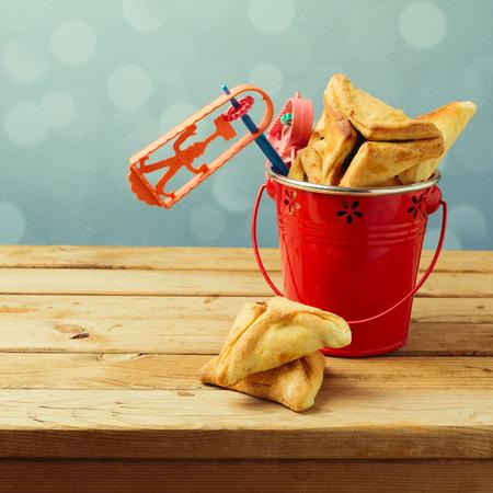 noise maker: Hamantaschen cookies in bucket with grogger noise maker