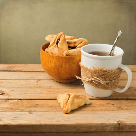 haman: Hamantaschen cookies with cup of tea on wooden table Stock Photo