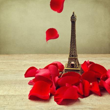 Petite tour Eiffel avec des pétales de rose sur la table en bois