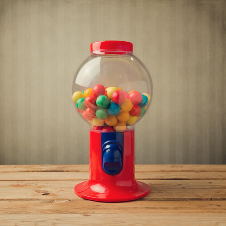 gum: Gumball machine on wooden table over retro wallpaper Stock Photo