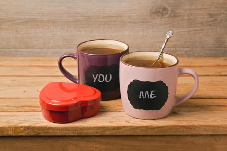 나무 테이블에 칠판 스티커와 차 컵의 커플