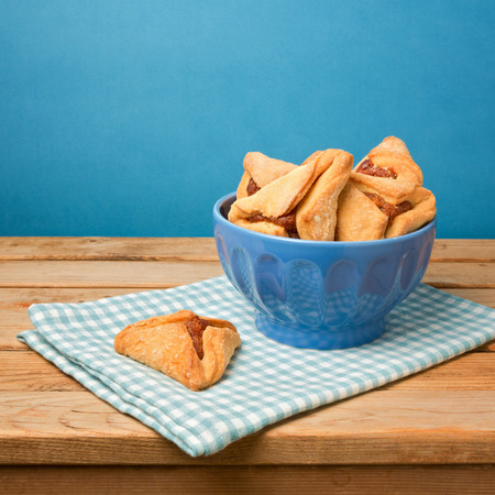 hamantaschen: Hamantaschen cookies for Jewish festival of Purim on wooden table over blue background Stock Photo