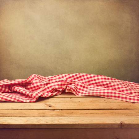 tablecloth: Empty wooden deck table with tablecloth over grunge background