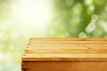 mesa de madera: Mesa de madera vacía sobre jardín de fondo bokeh Foto de archivo