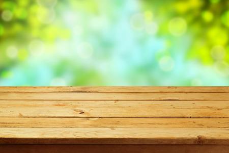 Empty wooden deck table over garden bokeh background Stock Photo
