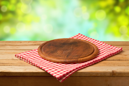 picnic table: Round board on tablecloth on wooden table over bokeh background. Stock Photo