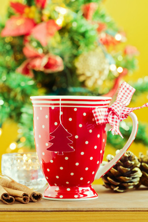 Cup of tea over bokeh Christmas tree background photo
