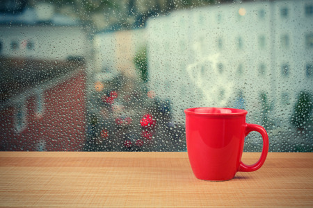 Cup with hot drink in front of rainy day window