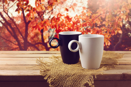 White and black cup with beverage on wooden table over beautiful nature background Archivio Fotografico