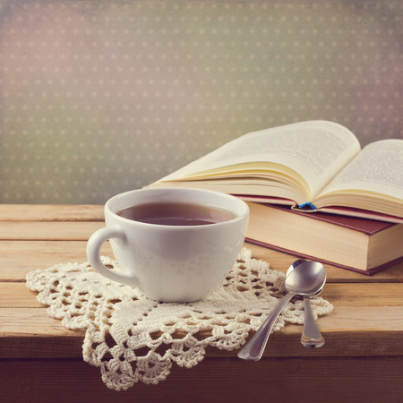 tea filter: Cup of tea on crochet doily and vintage books with retro filter effect Stock Photo