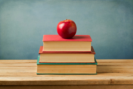 Back to school concept. Apple on vintage books