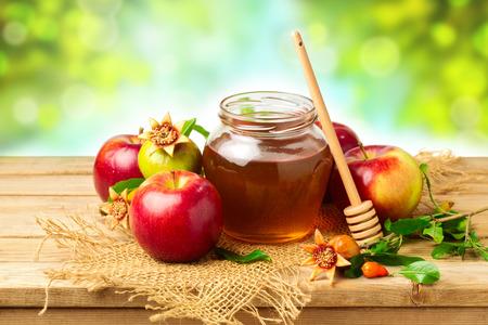 나뭇잎 배경 위에 나무 테이블에 꿀, 사과와 석류