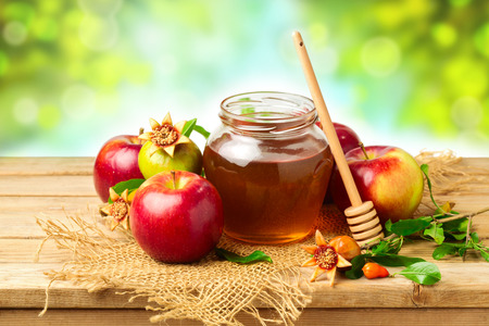 honey jar: Honey, apple and pomegranate on wooden table over bokeh background