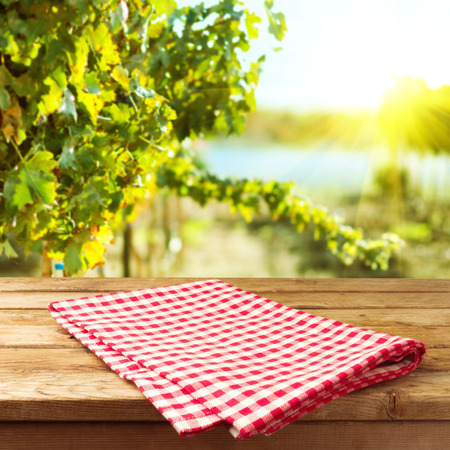 Empty wooden deck table with tablecloth over vineyard bokeh background Stock Photo