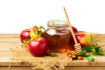 jewish background: Honey, apple and pomegranate on wooden table over white background