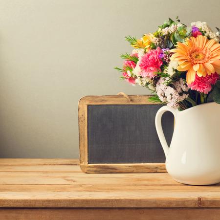 ramo de flores: Ramo de la flor y la pizarra en mesa de madera Foto de archivo