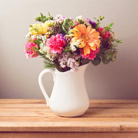 bouquet fleur: Bouquet de fleurs dans cruche blanche sur la table en bois