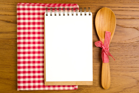recipe card: Blank note book with wooden spoon on tabletop