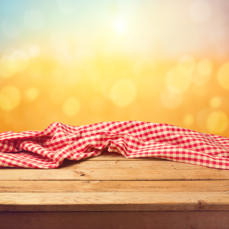 picnic cloth: Empty wooden deck table with tablecloth sunset bokeh background