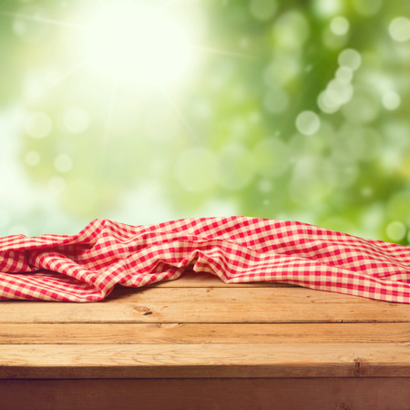red kitchen: Empty wooden deck table with tablecloth over green bokeh background
