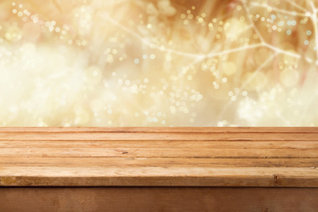 empty table: Golden bokeh with empty wooden table for product montage display Stock Photo