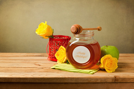 jewish food: Honey, apple and flowers on wooden table. Jewish New Year celebration.