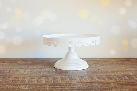Cake plate on vintage wooden table over bokeh  Stock Photo