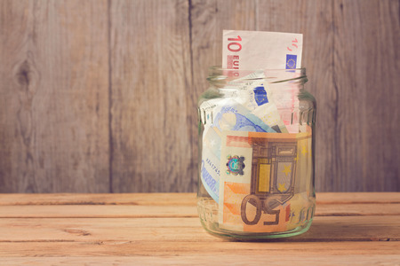 dinero euros: Money in glass jar on wooden table
