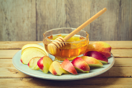 sliced: Honey and sliced apple on plate over wooden background for Jewish New Year Rosh Hashahah