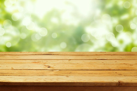 wooden deck: Empty wooden deck table over garden bokeh background. Ready for product montage display Stock Photo