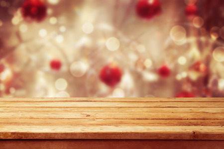 festivity: Christmas holiday background with empty wooden deck table over winter bokeh