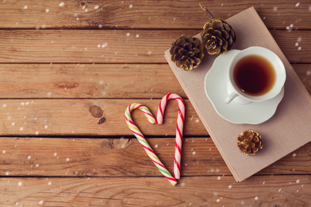 tea mug: Christmas holiday tea cup on old books with candy on wooden table with copy space