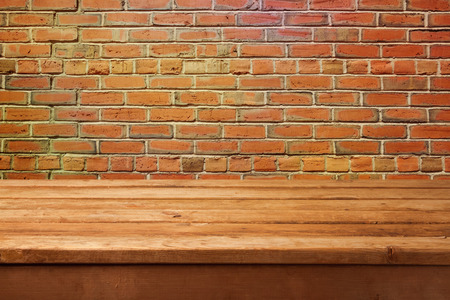 empty table: Empty wooden table and brick wall