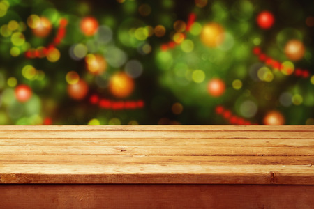 defocused: Christmas holiday background with empty wooden deck table over festive bokeh