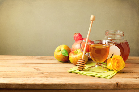 Honey and apple on wooden table
